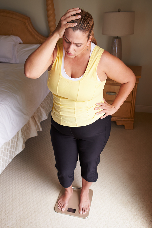 Overweight Woman Weighing Herself On Scales In Bedroom